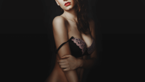 Cleavage shot of girl on black background with bra strap hanging down